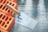 Fotografia Mattoni arancioni vernice raschietto sul concetto di muratura di tavola di legno