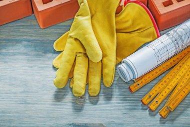 Set of red bricks safety gloves blueprints wooden meter on wood