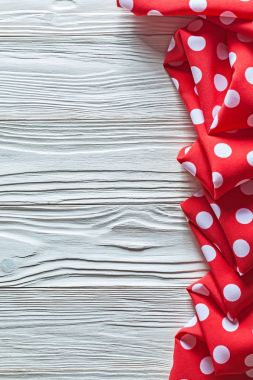 Red folded polka-dot tablecloth on wood board