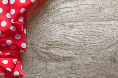 Red white cotton folded polka-dot fabric on wooden board