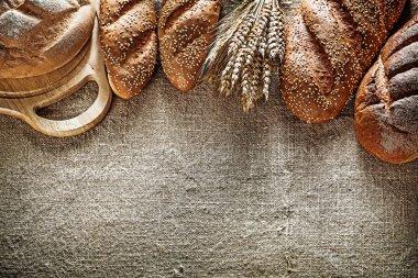 Chopping board brown bread baguette wheat ears on burlap backgro