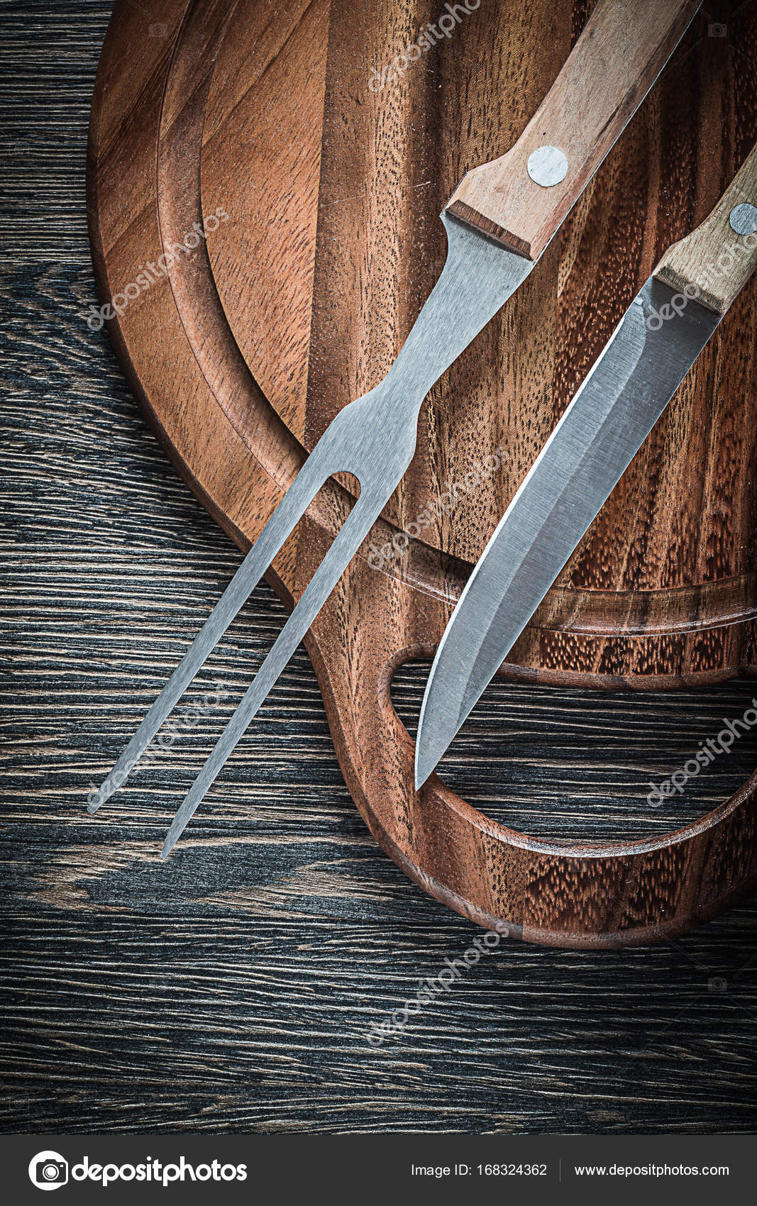 planche à découper couteau fourchette viande sur fond de bois