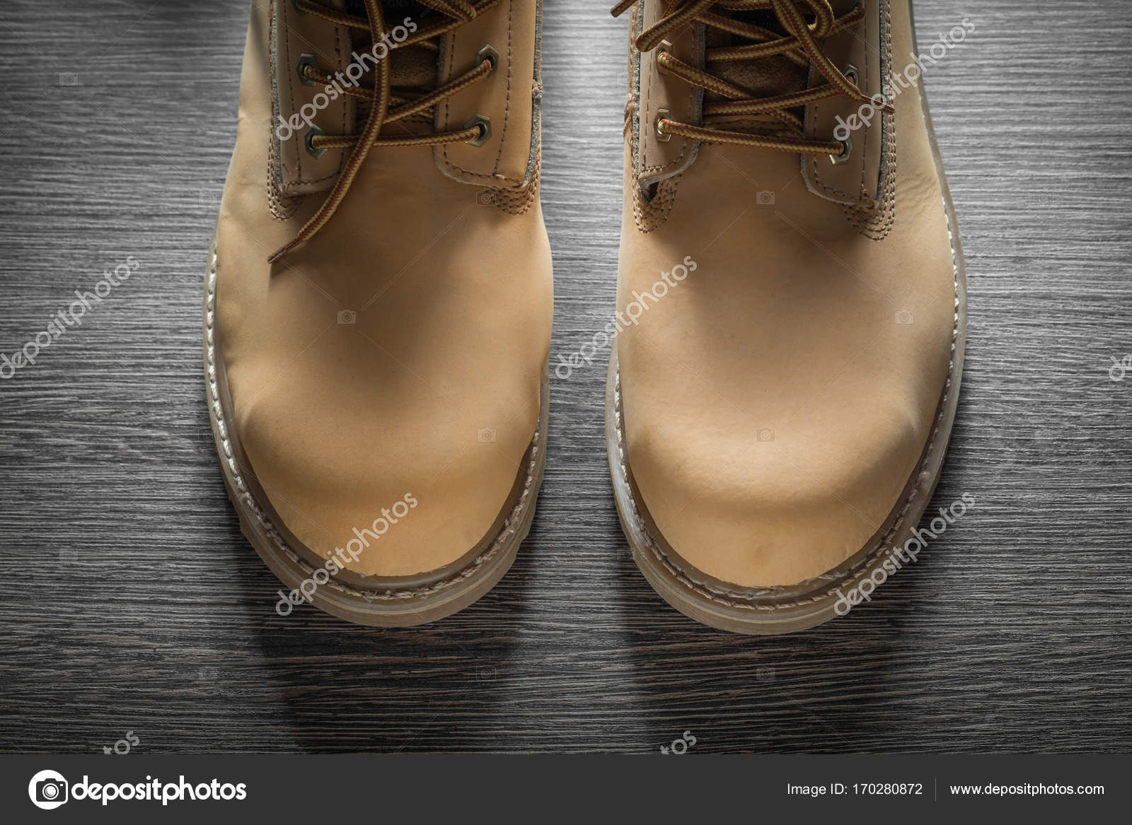 2b251dd8904 Ζευγάρι των αδιάβροχες μπότες εργασίας στην ξύλινη σανίδα– εικόνα αρχείου