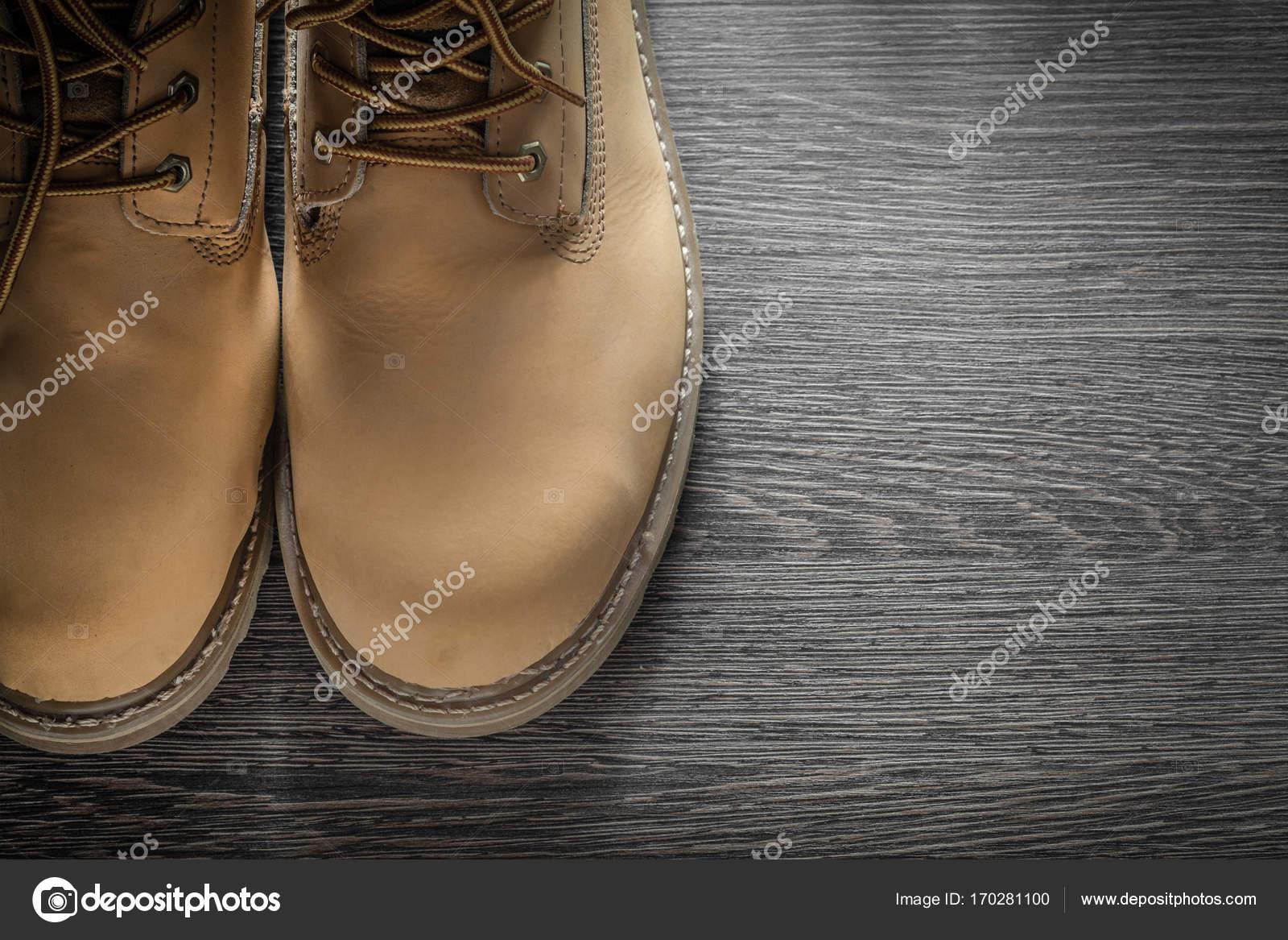 a663e6f7c3e Ζευγάρι ασφάλεια δερμάτινο κορδόνι μπότες για ξύλινη σανίδα– εικόνα αρχείου