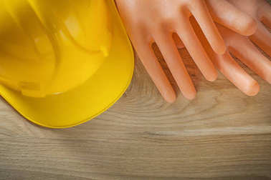 Dielectric gloves hard hat on wooden board