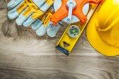 Fotografie Construction level protective gloves measuring tape hard hat on