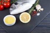 Syrové ryby dorado vaření a ingredience. Dorado, citron, rajče, byliny a koření. Pohled shora na dřevo tabl
