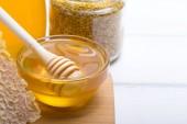 Medu ve sklenici s medem naběračka na dřevěné pozadí