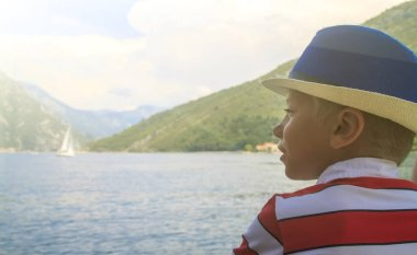 boy in a blue hat sails on a ferryboat across the Bay of Kotor and enthusiastically looks into the distance to the mountains and a sailing boat