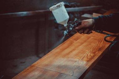 Master painting wood with spray gun