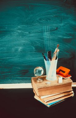 Old blackboard with school supplies