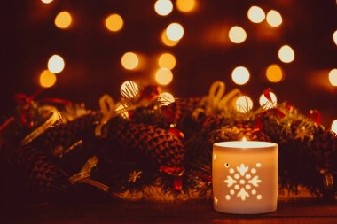 Christmas lantern with burning candle and garland