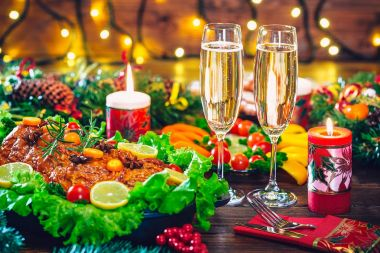 Christmas table setting with roasted meat decorated in Christmas style with champagne glasses