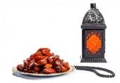 La festa musulmana del mese santo di Ramadan Kareem. Bellissimo sfondo con una lanterna brillante Fanus e datteri secchi su bianco. Spazio libero per il vostro testo