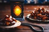 La festa musulmana del mese santo di Ramadan Kareem. Bellissimo sfondo con una lanterna brillante Fanus e datteri secchi su tavole di legno. Spazio libero per il vostro testo