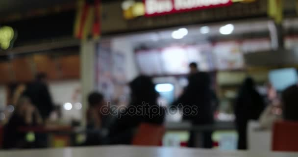 Blurred People in front of counter of fast food in food court of mall