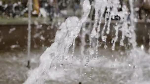 City park fontána pracující s lidmi na rozostřeného pozadí. Pomalý pohyb Vodní kapky a stříkance ve vzduchu