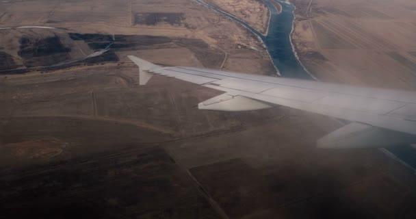 Křídlo letadla letícího nad zemí s jezery. Pohled z okna letadla. Retro barevné třídění