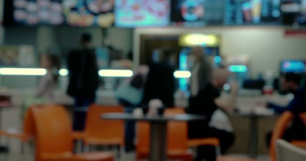 Defocused People in front of counter of fast food cafe in food court of shopping mall