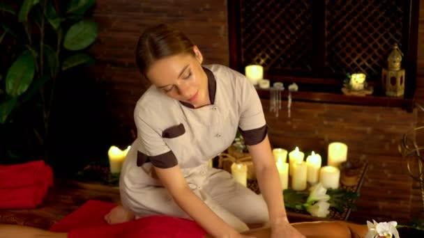 Žena leží na posteli dřevěný masážní lázně. 4k