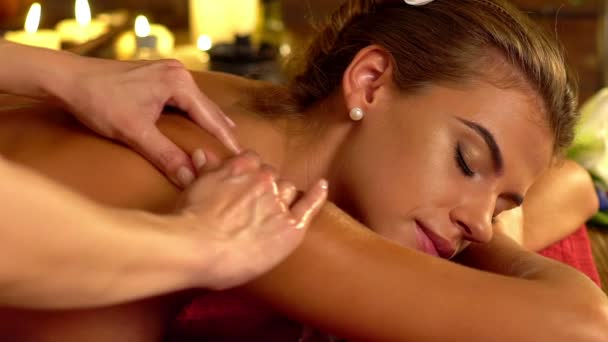 Woman lying on wooden massage spa bed. Slow motion.