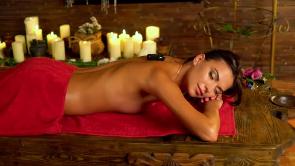Lastone therapy massage in spa salon. Masseuse hands with stone. 4k