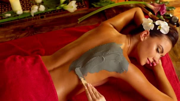 Massage and clay body mask in spa salon. Top view. 4k