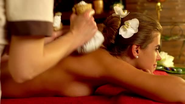 Young woman have hot exotic poultice massage in spa salon.4k.