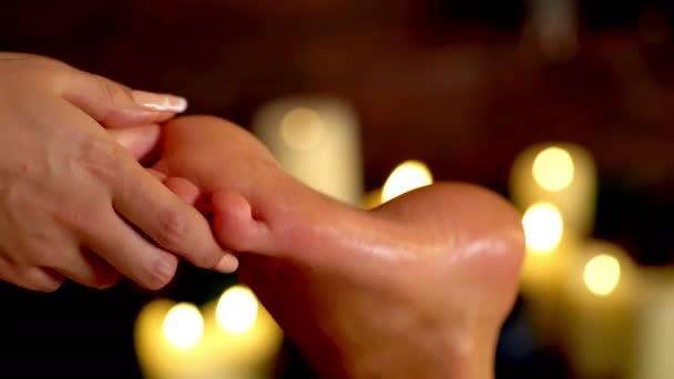 Nožní masáž terapie na svíčku, hořící pozadí. 4k