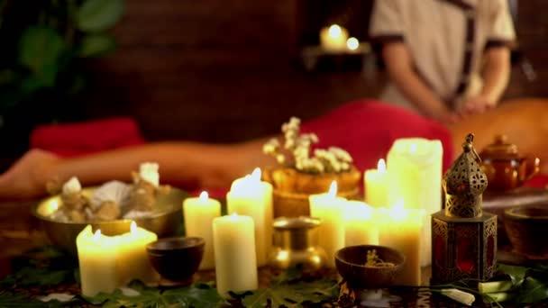 Zátiší s hořící svíčky a masáž byliny. 4k