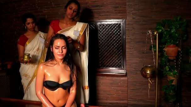 weiße Frau mit professioneller Kopfbehandlung. Indische Masseurin im Wellness-Salon.