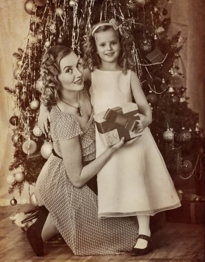 Family portrait of child with mother near Christmas tree.