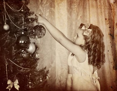 Retro old portrait of child decorate on Christmas tree.