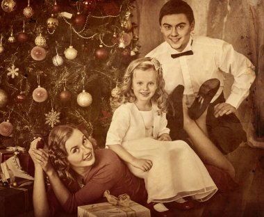 Family with children pose under Christmas tree.