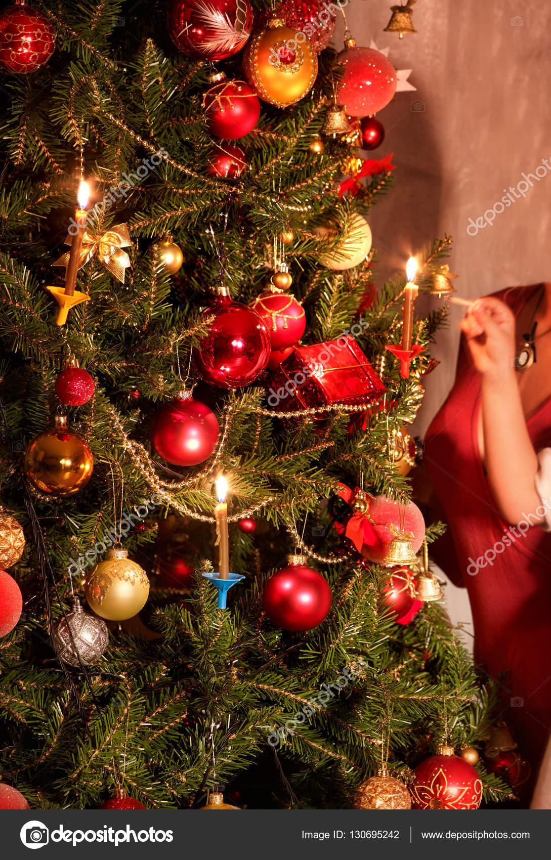 Dressing Christmas tree. Light candles . — Stock Photo © poznyakov ...