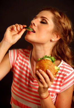 Girl in ecstasy enjoying a sandwich.