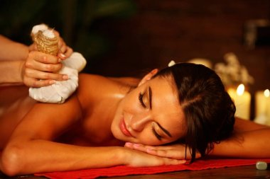 Massage woman spa salon. Female have herbs hot ball therapy.