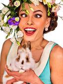 Fényképek Húsvét lány gazdaság nyuszi. Nő holiday tavaszi virágok frizura
