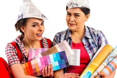 Repair home women holding color guide for wallpaper.