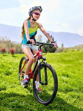 Woman traveling bicycle on green grass in summer park.
