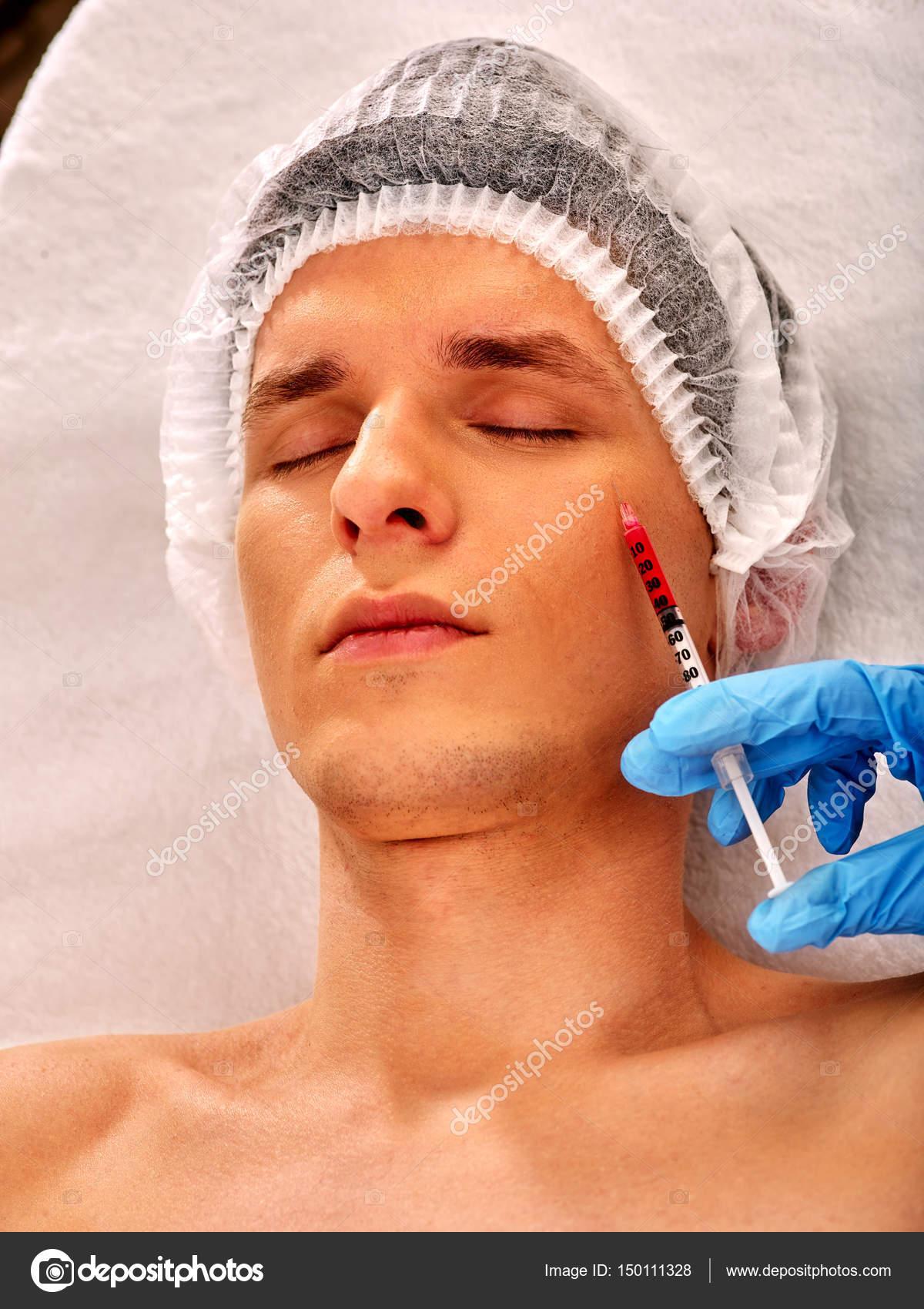 388965483bfec Injeção de enchimento para o rosto masculino. Plástica cirurgia estética  facial na clínica de beleza. Homem dando injeções de anti-envelhecimento  para puxar ...