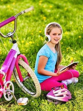 Bicycle child wearing headset listening music. Playing on tablet pc.