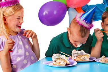 Birthday children celebrate party and eating cake on plate together .