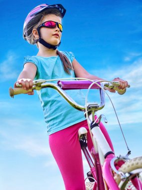 Child traveling bicycle in rainbow goggles and helmet in park.