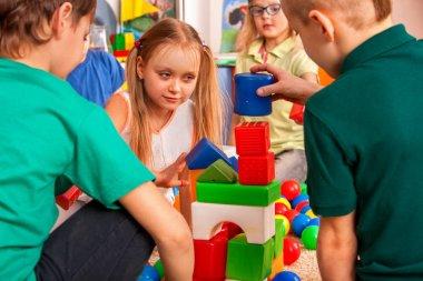 Break school of children playing in kids cubes indoor.