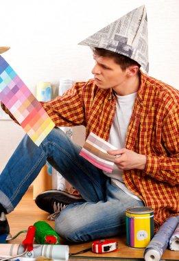 Repair home man holding paint roller for wallpaper.