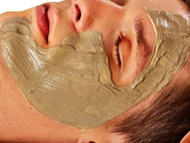 Mud facial mask of man in spa salon. Face massage .