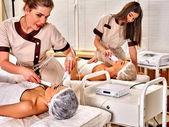 Obličejová masáž v salonu krásy. Elektrická stimulace pár produkty péče o pleť