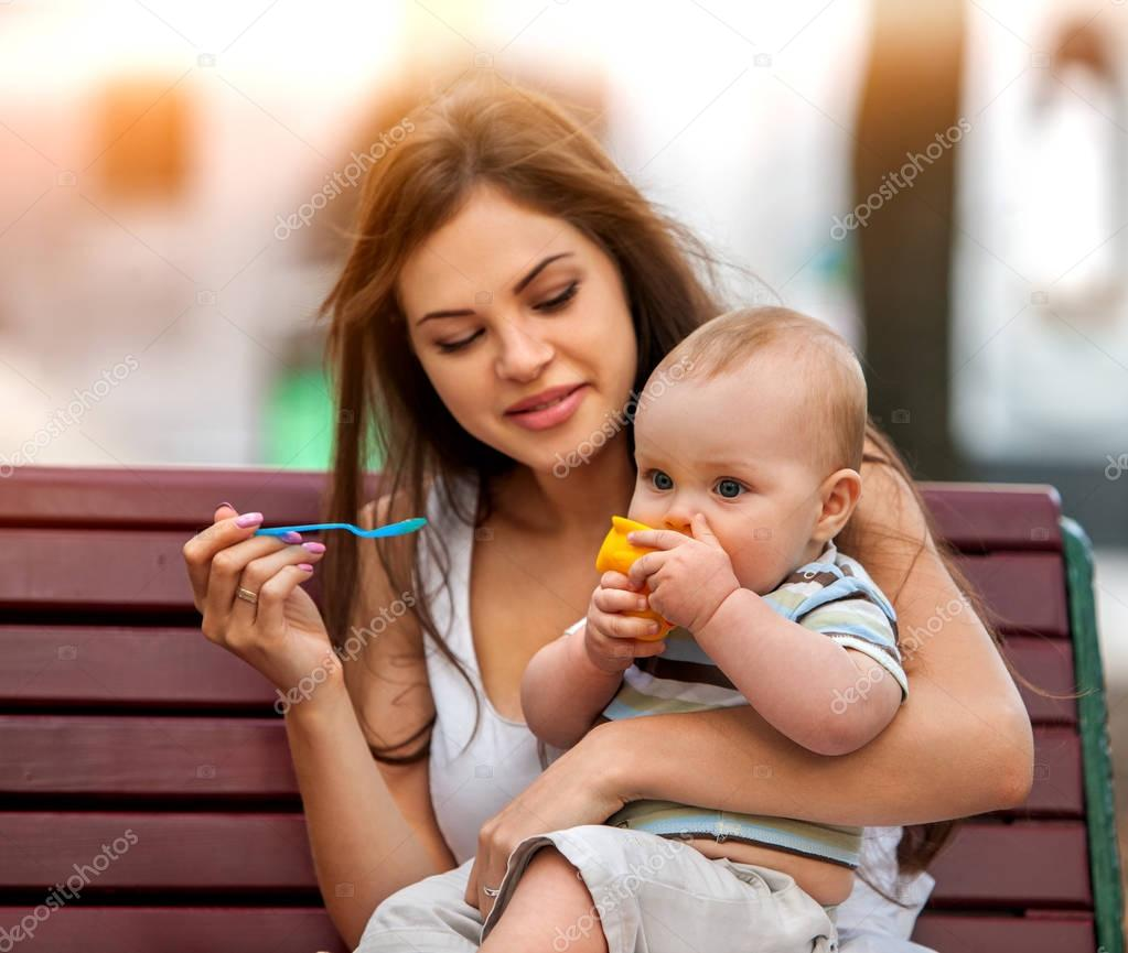 Baby feeding spoon by mother in park outdoor. Color tone.