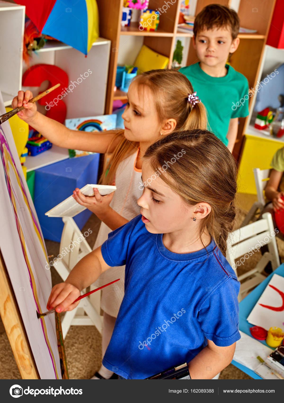Children painting finger on easel. Group of kids with teacher ...